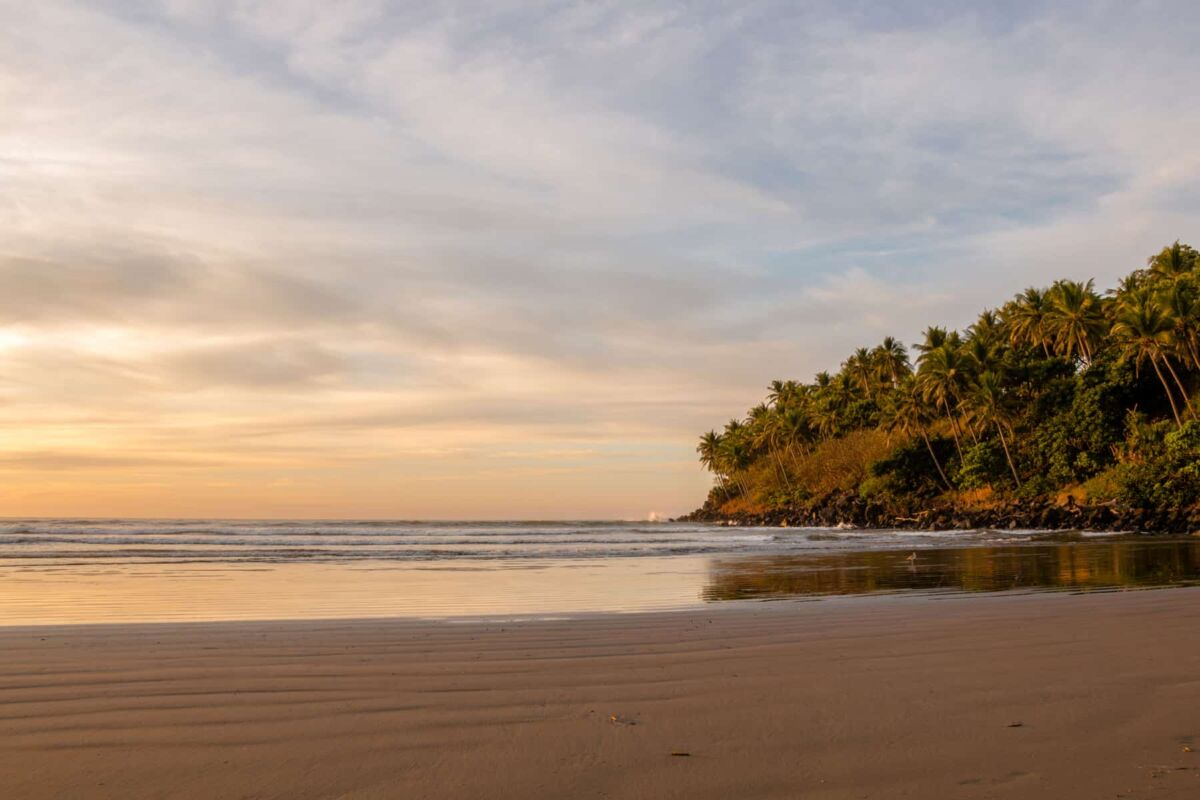 Sunset over a calm sandy beach with cliffs and palm trees in the background. El Cuco, El Salvador.