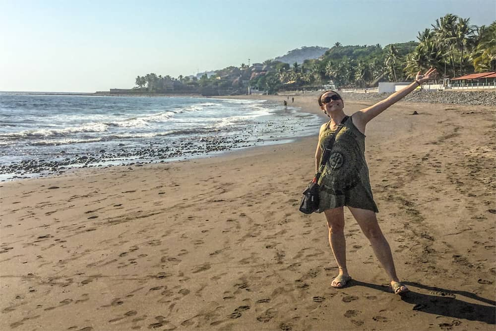 Woman standing happily on a sandy beach in El Salvador.