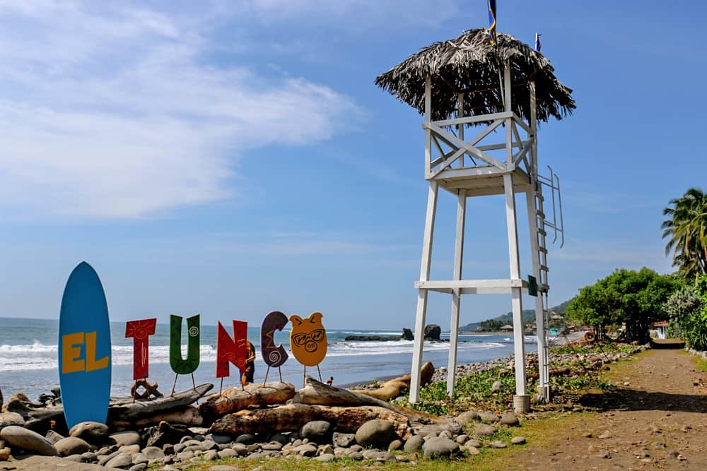 A wooden lifeguard tower on a beach beside a sign that reads 'El Tunco'