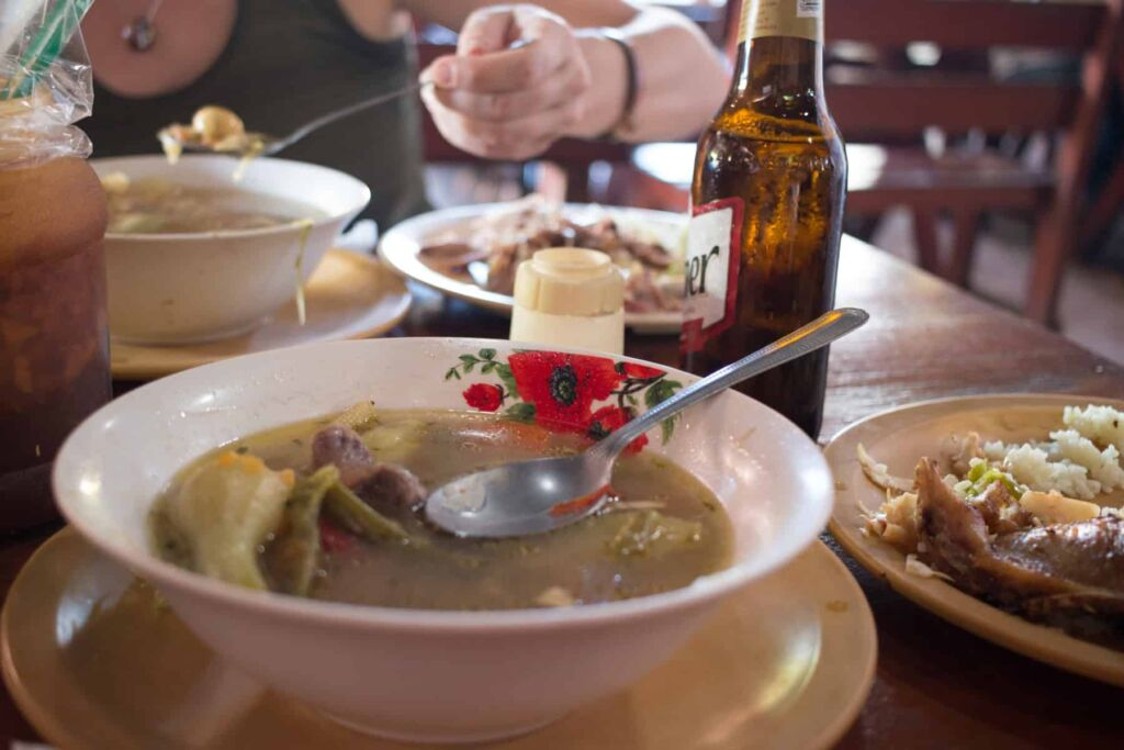 Bowls of soup and bottles of beer on a table.