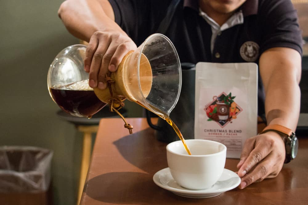 Man pouring coffee from a glass container.