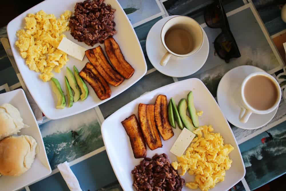 Plates of fried plantain, eggs, beans and eggs with cups of coffee.