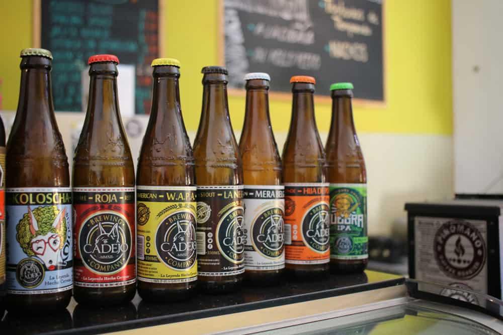Several bottles of beer ona shelf.