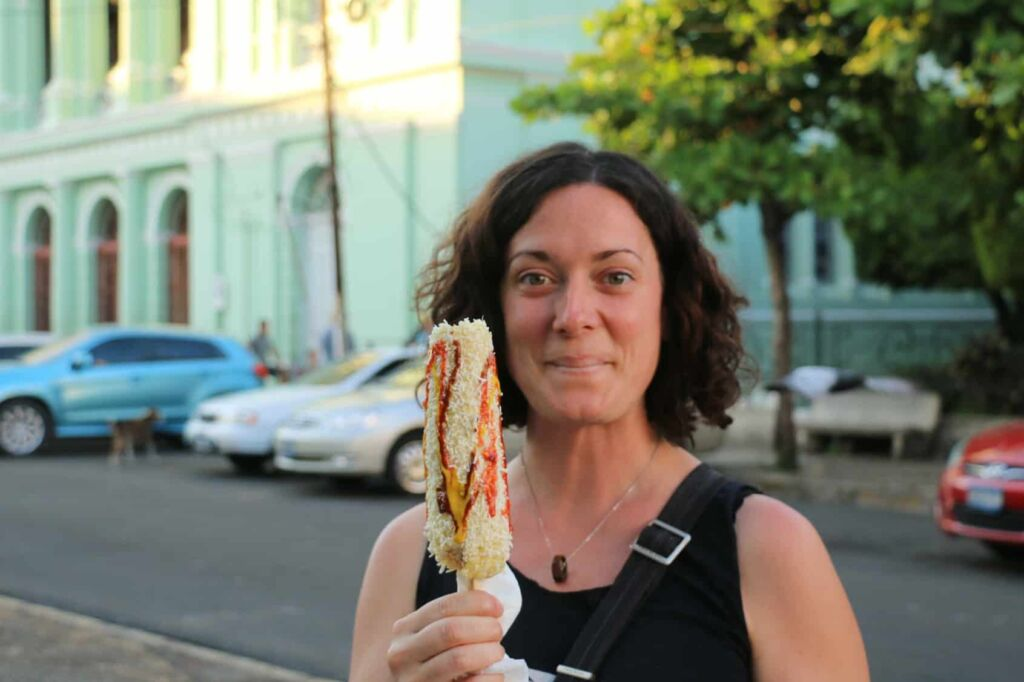 Woman holding a cob of corn covered in cheese and sauces.