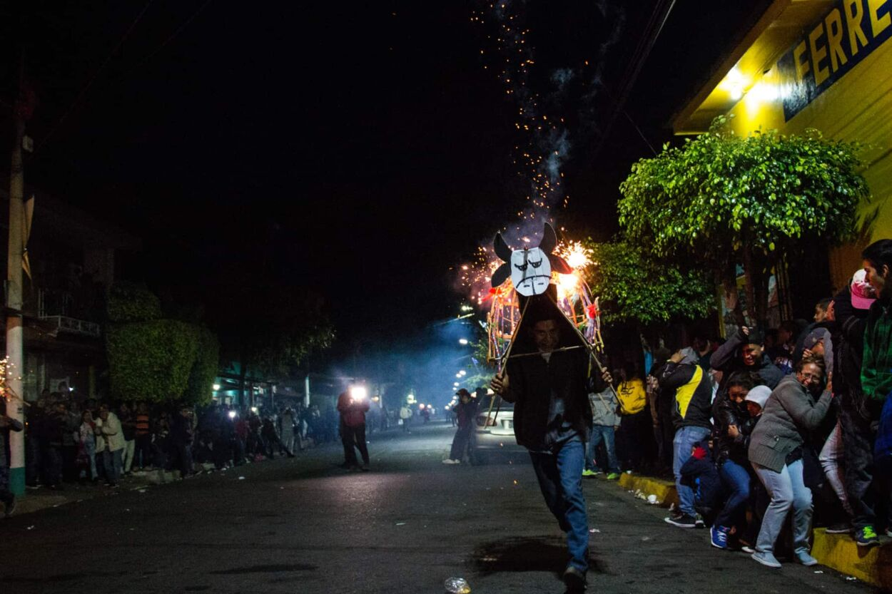 Man running towards the camera with fireworks flying from his wooden bull costume.