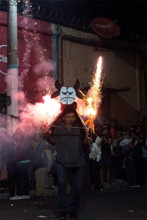 Man running in the street with fireworks shooting from his back.