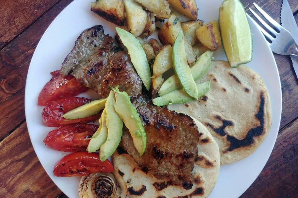 White plate with grilled meat, tortillas, tomatoes and avocado.