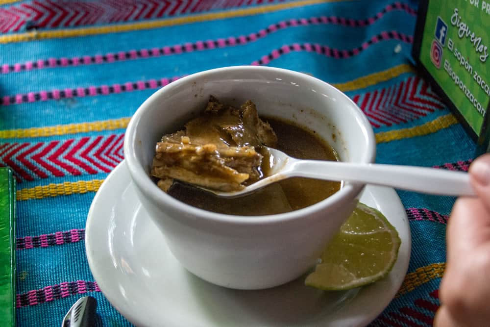 Small bowl of soup with a spoon holding some meat.