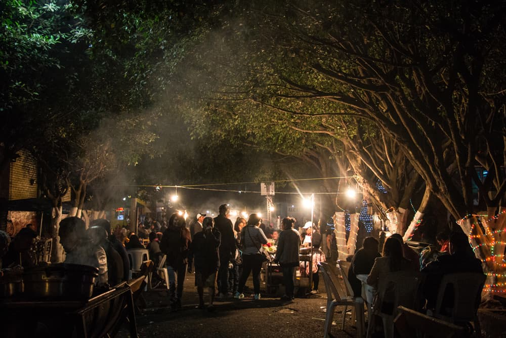 People on a street at night surrounded by smoke from charcoal grills.