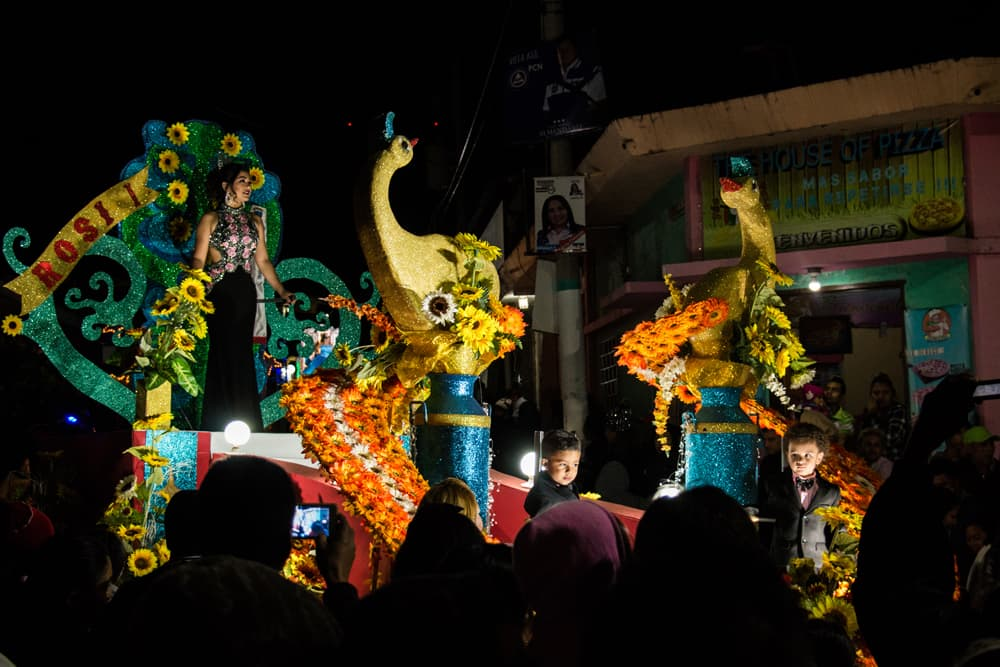 Colourful parade float during the night with a beauty pageant contestant on top.