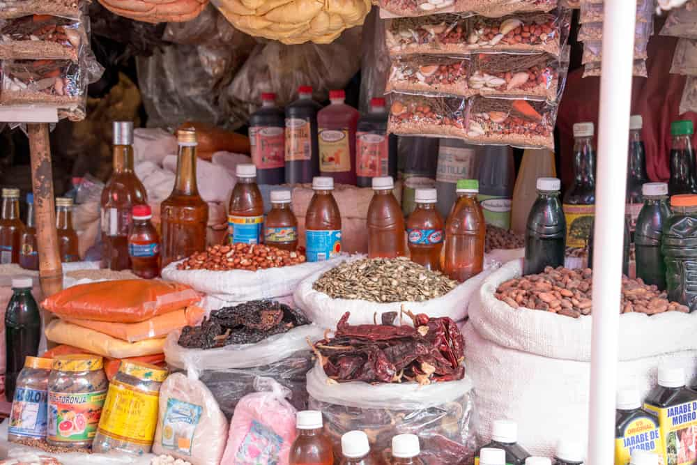 Different sauces and bangs of dry spices in a market.