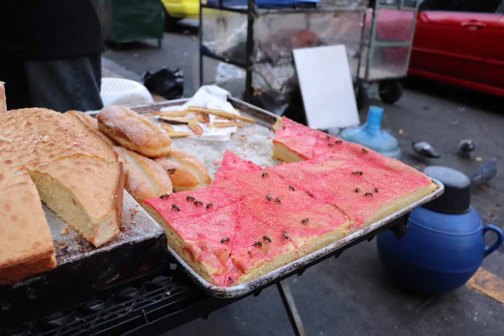 Pastries on display outside on a large sheet pan. One of them is covered in bees.