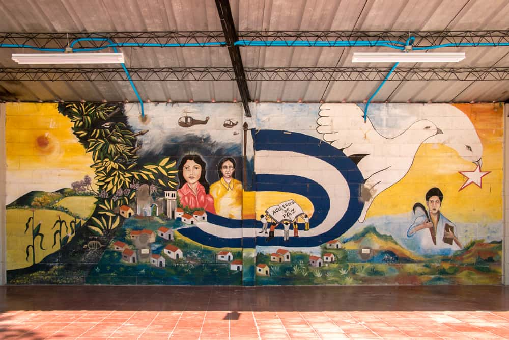 Mural on a wall depicting scenes from the conflict and a dove for peace.