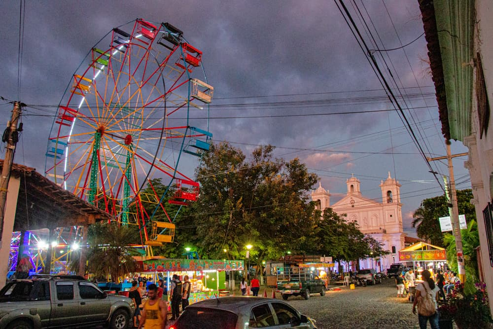 Ferris wheel in front of a large cathedral at dusk.