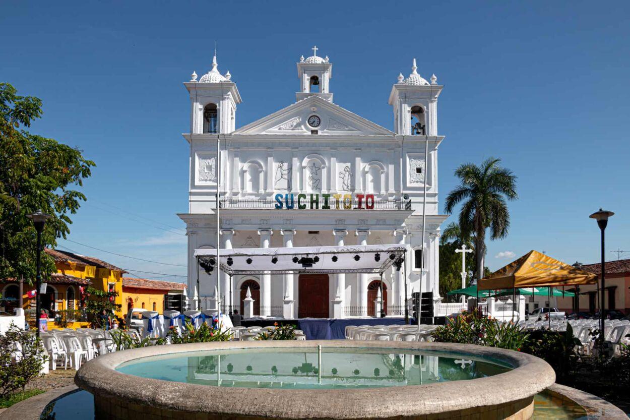 White colonial church behind a blue fountain.