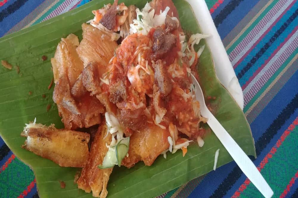 Fried yuca root with stewed meat and a red salsa.